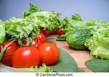 Home grown and harvested vegetables on wooden table background. Fresh lettuce, salad, tomato, radish, spinach and cucumber. Healthy eating lifestyle
