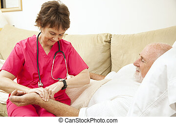 Home Health Nurse Takes Pulse - Home health nurse taking the...
