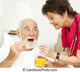 Home health nurse giving medicine to a senior patient.