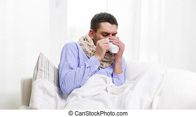 home, healthcare and medicine concept - ill man with flu drinking hot tea at home