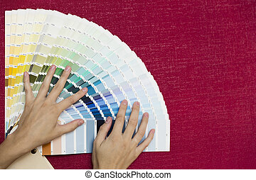 Home improvement. Beautiful women choosing a color from color palette. Renovating a room.