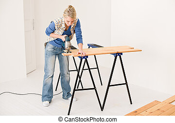 Home improvement - handywoman cutting wooden floor with ...