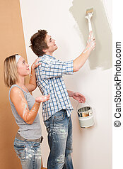 Home improvement: Man painting wall with paintbrush