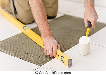 Home improvement, renovation - handyman laying tile with...