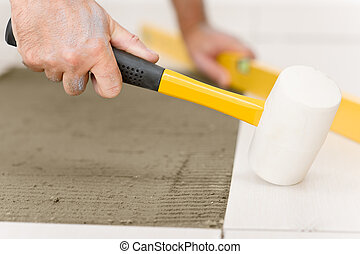 Home improvement, renovation - handyman laying tile with...