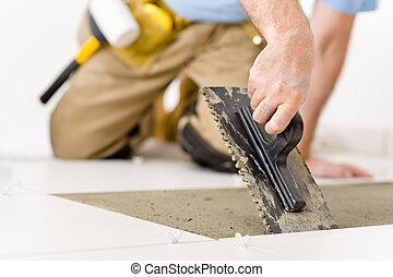 Home improvement, renovation - handyman laying tile, trowel...