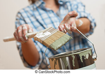 Home improvement: Woman holding paint brush and can