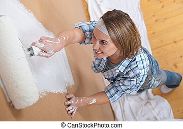 Home improvement: Woman painting wall with paint roller