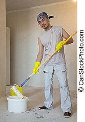 Home improvement. Young man painting ceiling