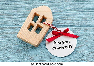 Home insurance concept with wood house and paper  tag