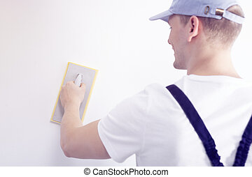 Home interior renovation handyman smoothing down a white wall with a sandpaper tool