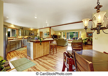 Home interior with hardwood floors and open floor plan showing dining room, kitchen, and living room.