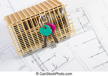 Home keys and small house under construction on electrical drawings, building home concept