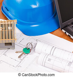 Home keys, small house, electrical diagrams with laptop for engineer jobs on desk, building home concept