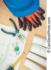 Home keys with electrical diagrams or drawings, protective helmet with gloves and work tools, building home concept