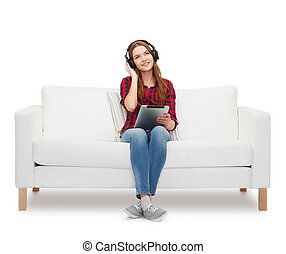girl sitting on sofa with headphones and tablet pc - home, ...