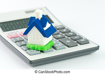 Miniature house model with calculator isolated on white background