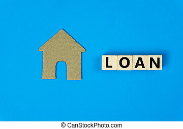 Home loan concept. A small house model made by paper cut with wooden block on blue background. Depicts loans for the build or purchase of new homes.