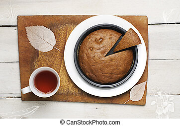 Home made banana cake with cup of tea on white background. Cake as a Pack man (old fashioned computer game).