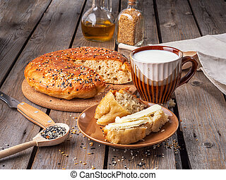 Home-made bread in a cut and a slice of sliced bread smeared with butter and a mug of milk on a plank rustic table, next to wooden spoons with flax and sesame seeds. In the background are seasoned jars.