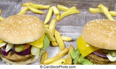 Home made burgers next to french fries on wooden background