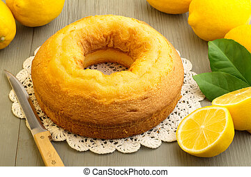 home made cake - cake and yellow lemons on wooden board