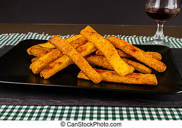 Home made cheese straws on plate on slate, side view.