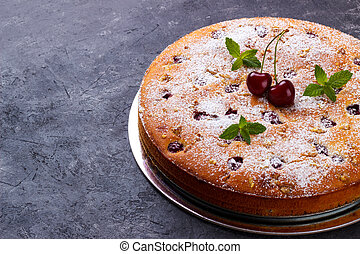 Home made cherry cake with icing sugar and mint over black rustic background