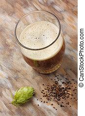 Home made dark beer with its preparation ingredients