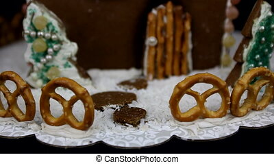 Detail of home made gingerbread house with christmas trees on black background