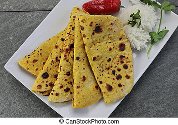 Home made Gluten free Chickpea flour Roti or Besan Roti or Chapati or bread on a plate .
