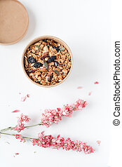 Home made granola cereal flakes with dried fruit, nuts and honey in a craft paper box with dried flowers on white table.