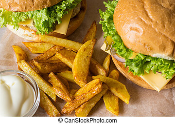 Home made hamburger with chicken, onion, cucumber, lettuce and cheese on wooden table with potato fries