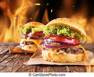 Fresh home-made hamburgers served on wooden planks. Fire flames around
