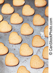Home made heart shaped cookies on baking tray