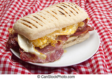 Home made panini. - Home made panini with egg and bacon on a...