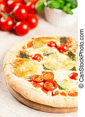 Home made pizza on wooden board with tomatoes on background