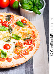 Home made pizza on wooden board with tomatoes
