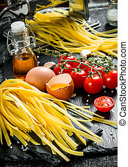 Home made raw pasta with eggs, tomatoes and oil in a bottle.