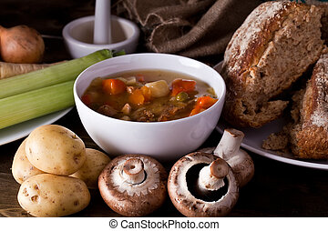 Home made soup and fresh vegetables with rustic bread