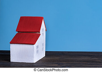 Home model on blue background. Loan concept. Side view