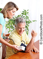Home monitoring of blood pressure - Seniors couple at home ...