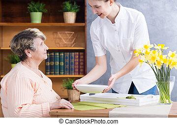 Home nurse serving soup - Caregiver serving nutritious soup...