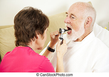 Home health nurse checks a patient's throat with an otoscope.