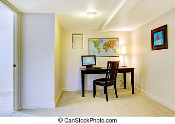Home office desk with map on the white wall.
