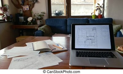 Home office. Table with laptop, house plans and notebook.