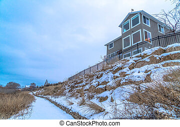 Home on the snowy shore line of Utah Lake with cloudy blue sky background