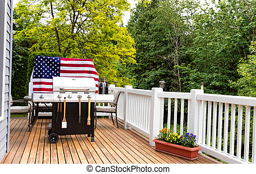 Home outdoor patio with BBQ cooker preparing for holiday picnic with trees in background