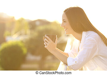 Home owner relaxing drinking coffee in a balcony - Side view...