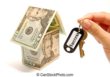 Home ownership - Hand holding a golden key with a success...